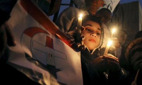 An Egyptian boy  in Cairo, Egypt, Friday, Jan. 7, 2011, during a candlelight vigil in mourning for t