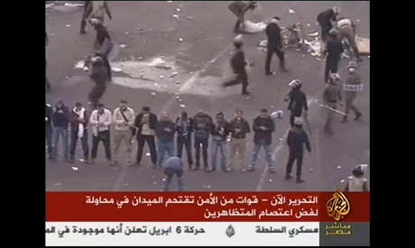 Protesters perform Sunset prayers while the army invades Tahrir square (Al Jazeera TV)