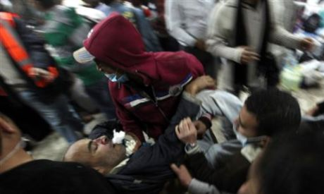 Protesters rushing towards the field hospital in Tahrir square carrying a wounded man after military