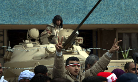 An anti-government protesters flashes a victory sign next to an army soldier positioned on his armor