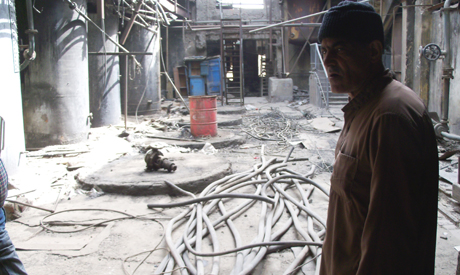 A worker stands next  to rubble