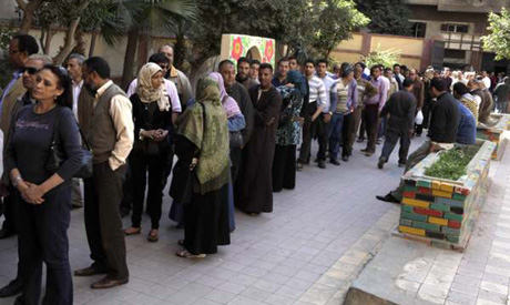 Egyptians queue to cast their vote during a national referendum, at a school in Cairo
