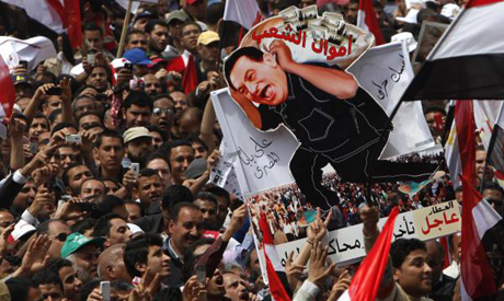 Protesters hold up a caricature of ousted president Hosni Mubarak carrying