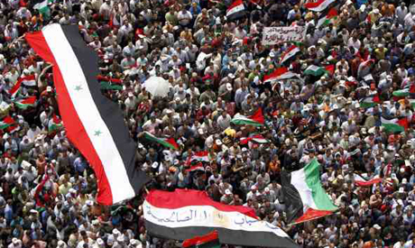 People hold up Syrian and Palestinian national flags during a demonstration at Tahrir Square in Cair