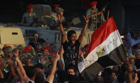 Demonstrators shout slogans as they clash with loyalists of ruling military council in Cairo