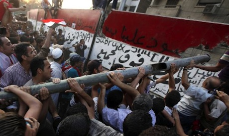 Egyptian protesters breaking down concrete wall before Israeli embassy