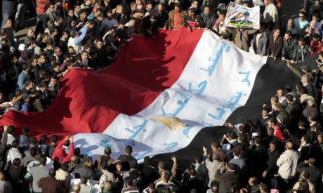 Egyptian protesters shout anti-military council slogans as they hold the national flag in Tahrir squ