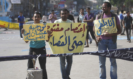 """Demonstrators hold banners with Arabic words that reads """" Open strike there is retribution"""" center,"""