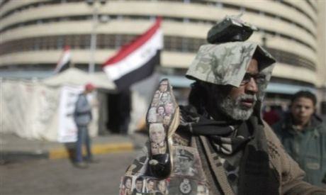 An Egyptian protestor displays a shoe decorated with pictures of Egypt
