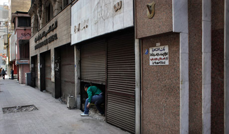 An Egyptian man emerges from a closed shop
