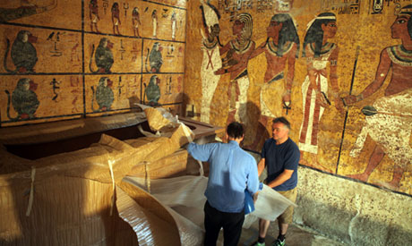 Ward removing the plastic cover to unveil the replica sarcophagus of Tutankhamun, photo by Sherif So