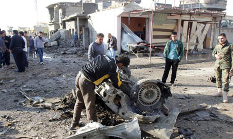 Resident inspects the site of a car bomb attack in Kirkuk