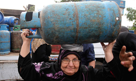 A woman carries a gas cylinder
