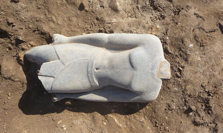 the newly discovered statue in situ covered with sand