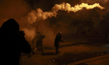 A protester throws back a tear gas canister during clashes near the interior ministry in Cairo (Phot