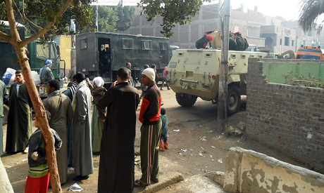 Security forces and bystanders are seen in Assuit, Egypt, Saturday, Dec. 31, 2011. (AP /Mamdouh Thab