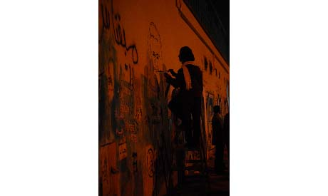 Artists paint the murals on Mohamed Mahmoud as the battle rages on ahead