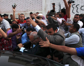 Men attack Egyptian presidential candidate Ahmed Shafik (C) as he leaves a polling station after cas