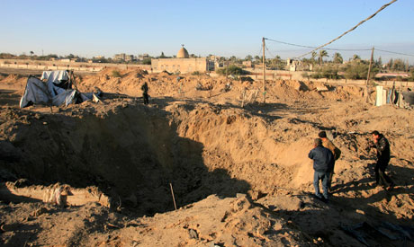Palestinians stand next to a crater following an Israeli air strike on a smuggling tunnel in Rafah (