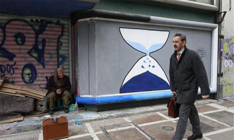 man sits in front of a closed shop with graffiti sprayed on its shutters in central Athens March 12,