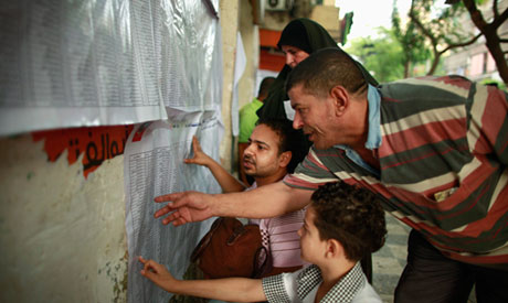 Voters check their names at a polling station in Cairo (Reuters)
