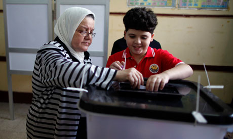 A voter with her grandson casts her vote at a polling station in Cairo (Reuters)