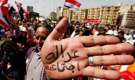 A protester holds up his palm during a protest for labour rights on Labour Day , in Cairo May 1, 201