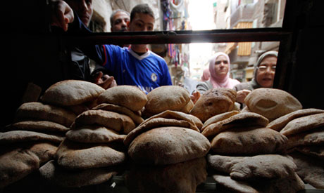 Egyptians buy bread from a bakery in Cairo