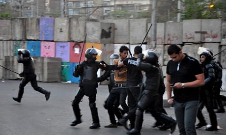 Egyptian riot police detain a protester
