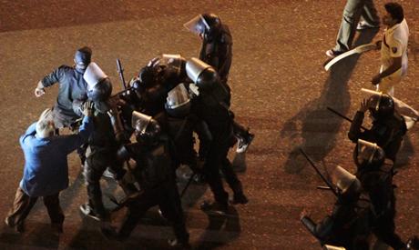 Riot policemen detain a protester