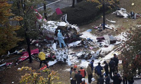 Police officers inspect the wreckage of a helicopter which crashed in Seoul