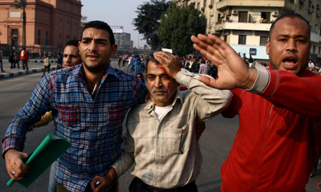 Protesters help an injured man during clashes