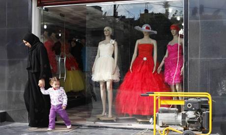 A Palestinian woman leaves a dress shop