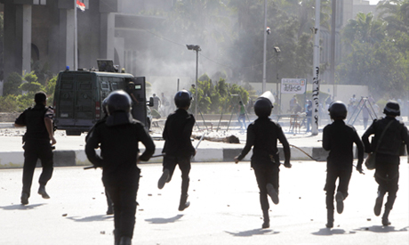 Riot police officers advance towards protesters at Al-Azhar University