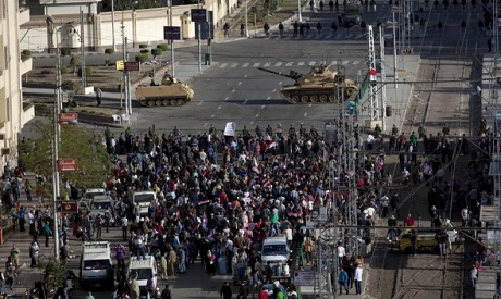 Egyptian army tanks secure the perimeter of the presidential palace while protesters gather chanting