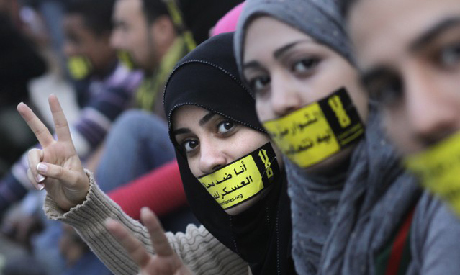 "File photo of Egyptian activists with stickers that read: ""No to military trials for civilians"" at a"