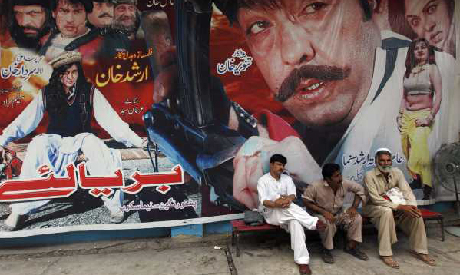 Cinema workers sit near a poster of a Pashto movie at Arshad cinema in Peshawar. (Photo: Reuters)