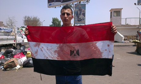 A man holding an Egyptian flag stained with bolld in Pro-Morsi sit-in in Cairo (Photo by:Bel Trew)