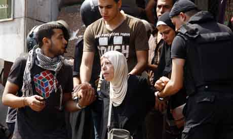 A protester who supports ousted Egyptian President Mohamed Morsi is escorted by police as she leaves