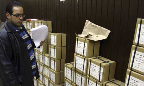 An election official stands next to boxes containing voting slips