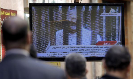 Egyptians watch television showing the trial of ousted Egyptian president Mohamed Morsi