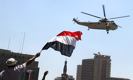 Egyptian flag as a military helicopter flies over Tahrir square