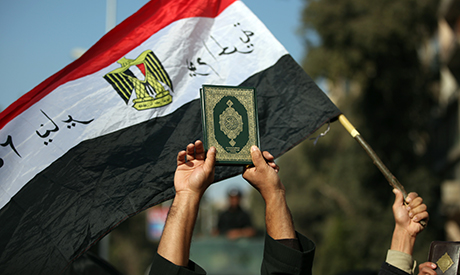 Egyptian man holds up the a copy of Quran