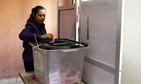 A woman casts her ballot in the final stage of a referendum on Egypt