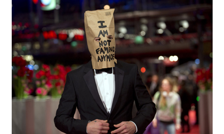 Actor Shia LaBeouf poses for photographers, with a paper bag over his head that says
