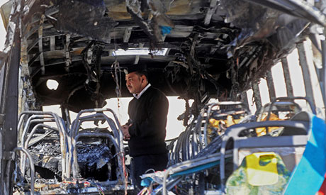 policeman inspects a damaged bus