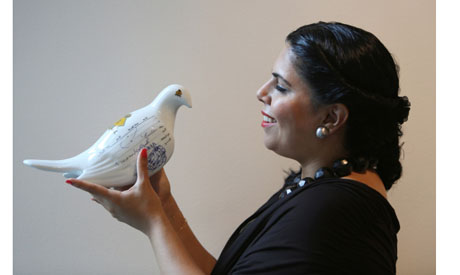 "Saudi artist Manal Al-Dowayan poses with one of her messenger pigeons of ""Suspended Together"" insta"