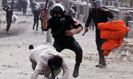 Riot policemen beat a protester