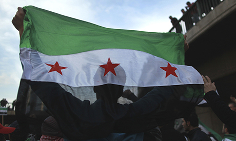 demonstrator holds a Syrian flag during a protest