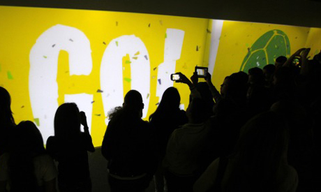 """Visitors watch a video during the World Cup """"Trophy Tour"""" in Sao Paulo"""
